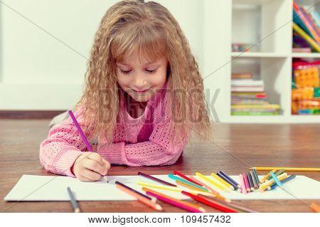 Little beautiful girl draws pencil on the floor in the nursery