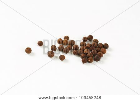 hadful of allspice berries on white background