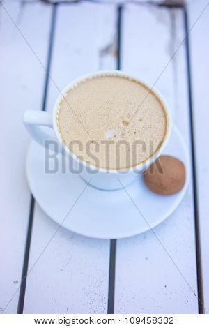 Top view of a Cup of hot coffee with cookie on old white table