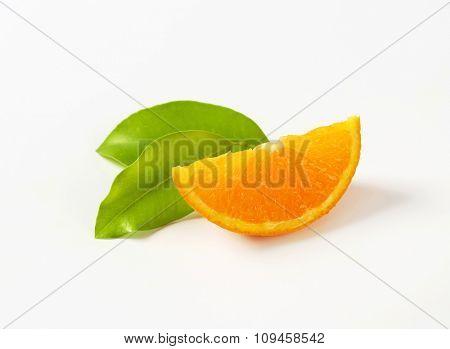 slice of fresh orange with leaves on white background