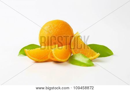 whole and sliced oranges with leaves on white background