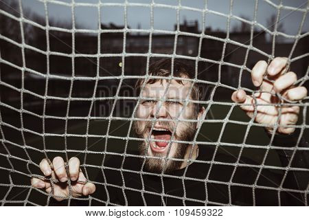 Energy furious bearded athlete screaming holding net