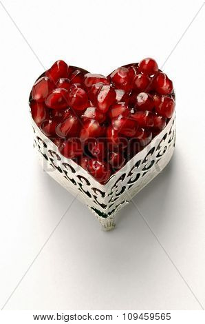 pomegranate seed in a heart shaped jewelry box