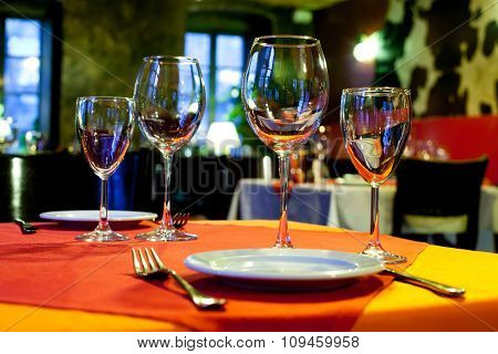Served table with a bright tablecloth, napkins, wine glasses and cutlery. colorful still life, servi