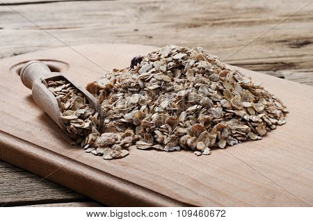 Heap Of Oat Flakes With A Scoop On Wooden Table