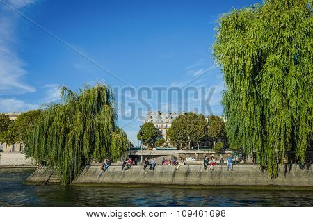 People rest on the banks of Ile St. Louis in Paris