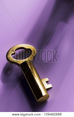 golden key and a keyhole shadow