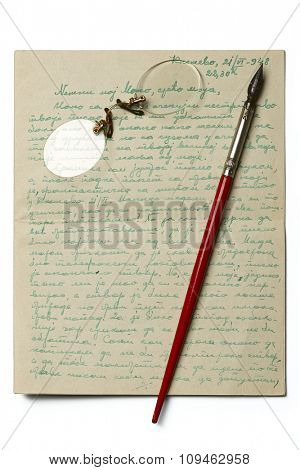 an old letter with a pair of rimless glasses and a calligraphy pen on it