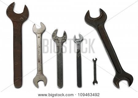 six old, rusty wrenches of different sizes on white