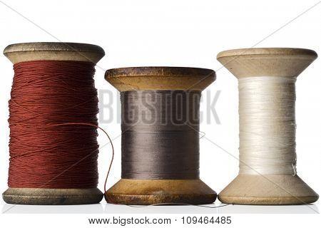 three spools of thread on white