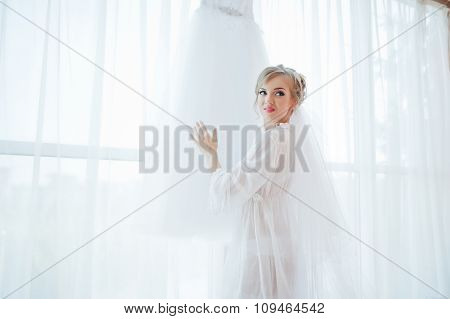 Gentle Bride In Gown Looked At Her Wedding Dress