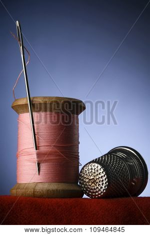 a wood spool of pink thread with the needle stuck in it and a thimble