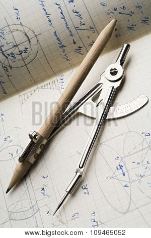 a pair of compasses on a trigonometry papers