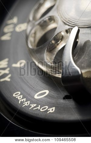 a detail of an old-fashioned rotary phone dial with shallow depth of field and focus on 0 for an operator