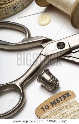 tailor's tools - scissors, spool of thread, measuring tape, needle, thimble, etc...