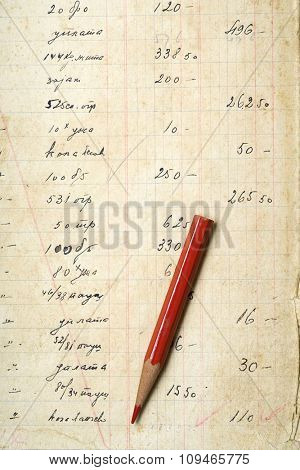 a red pencil on yellowed paper with accounting figures