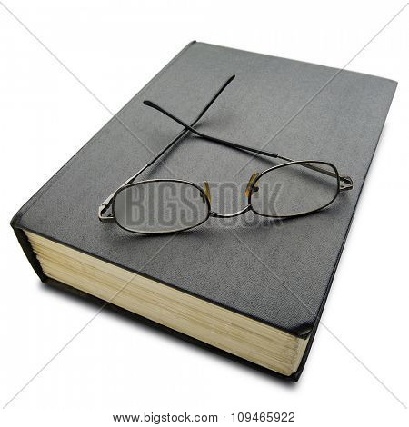 a pair of reading glasses on thick hard cover black book on white - with clipping path