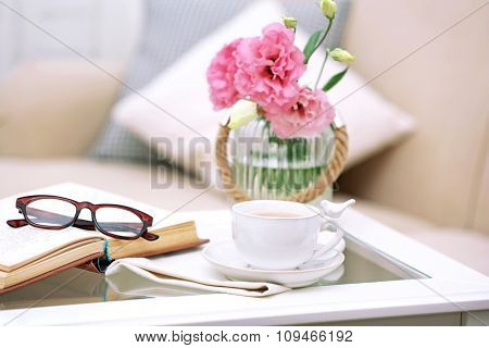 Cup of coffee with book on table in living room