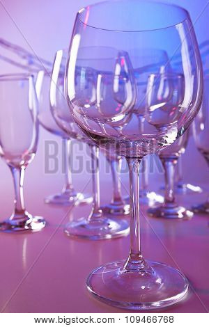 Empty wine glasses on color background