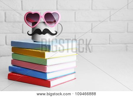 Books and cup with mustache on wooden table on brick wall background
