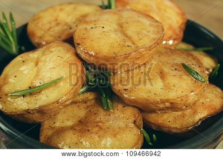 Delicious baked potato with rosemary in bowl close up