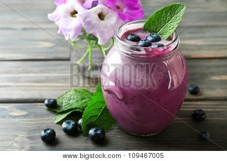 Glass jar of blueberry smoothie on wooden table, closeup