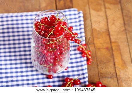 Fresh red currants in glass on table close up