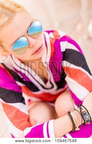 Beautiful blond woman in sunglasses on white sand