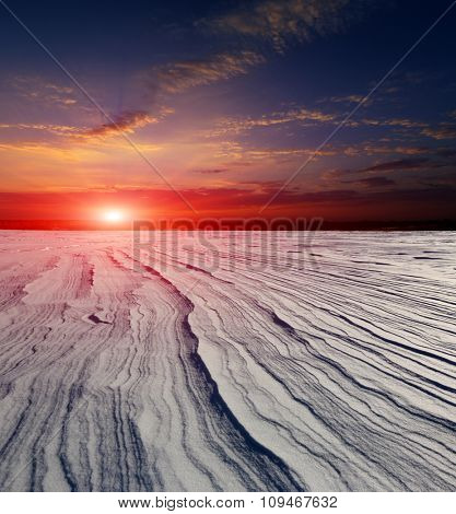 Landscape with sunset over frozen snow meadow