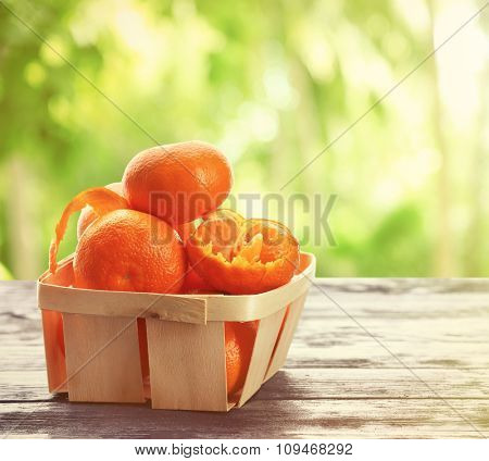Ripe tangerines on wooden table on nature background