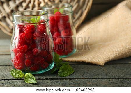 Sweet raspberries in glass jar on wooden  background