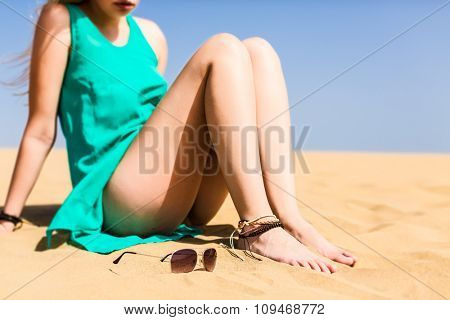 Young meditative  woman  wearing  short dress in  sand desert