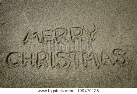 Merry christmas write in a sand at the beach