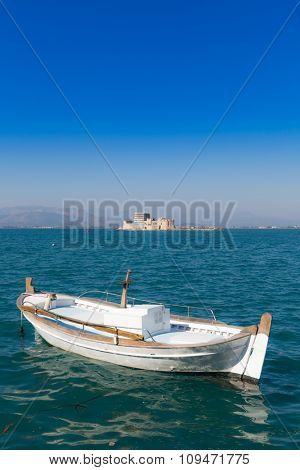 Seascape with fishing boat and Bourtzi castle in background, Nafplio, Greece