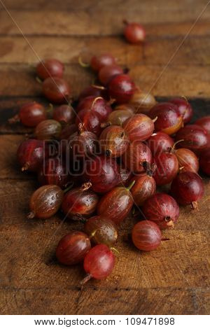 Red gooseberry on wooden table close-up