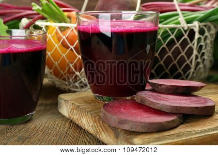 Glasses of beet juice with vegetables on table close up