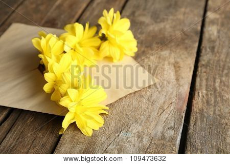 Yellow chrysanthemum in envelope on wooden background
