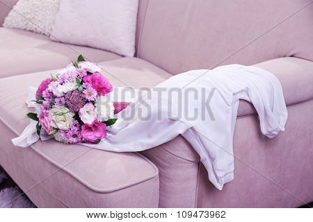 Wedding bouquet and bridesmaid dress on sofa in room