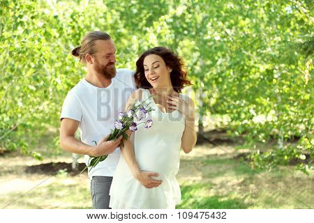 Handsome man gives a bouquet of pretty flowers to his lovely pregnant wife in the park
