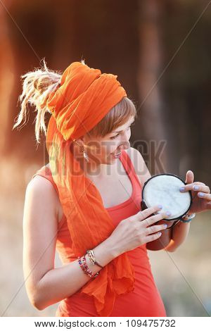 Portrait of pretty young woman playing djembe, close up
