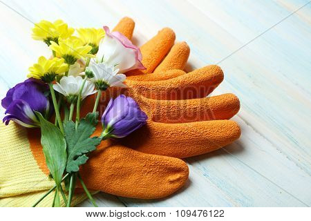 Beautiful composition of flower bouquet and garden gloves on light wooden background