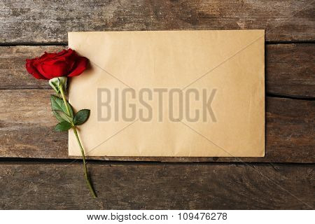 Blank card with beautiful rose on wooden background