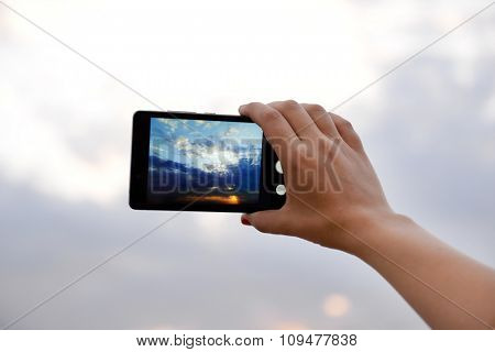 Woman using smart phone for taking photo of beautiful sky