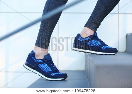 Sports woman legs in sneakers on stairs