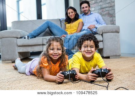Children playing video games on the carpet in living room while parents on the sofa
