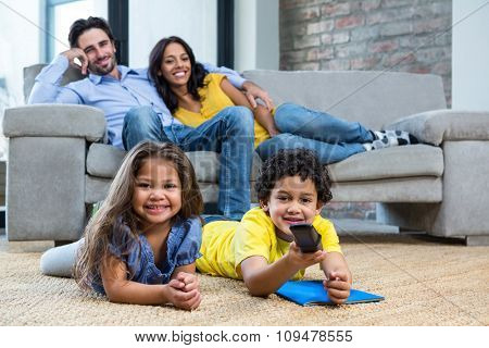 Smiling family in living room looking tv with children on the carpet