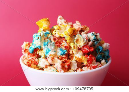 Sweet colourful popcorn on pink background