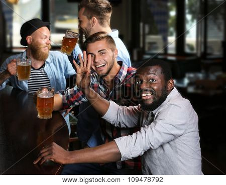 Happy friends having fun and drinking beer in pub