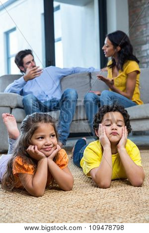 Children laying on the carpet in living room while parents talking on the sofa