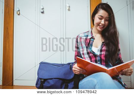 Smiling student sitting and reading a notebook at the university